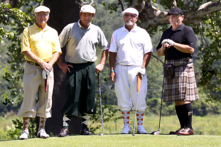 Group of four golfers posing for picture